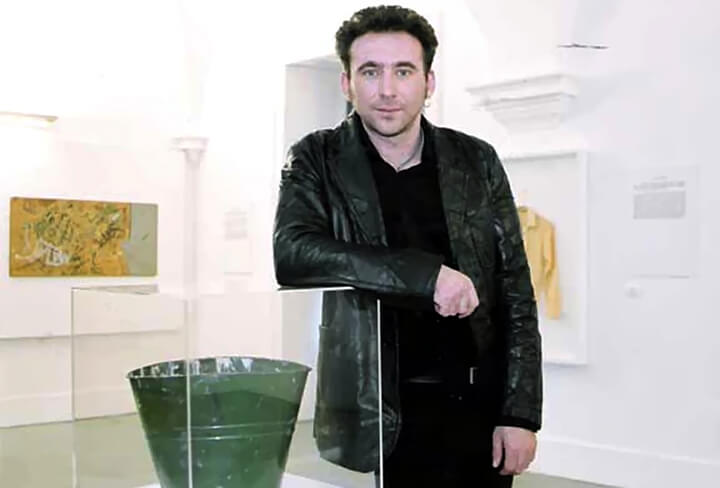 Guy Tarrant dressed in black, leaning against one of his artworks in a gallery